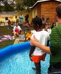 musician baptizing a neighbor girl with their backyard expression of the Body of Christ